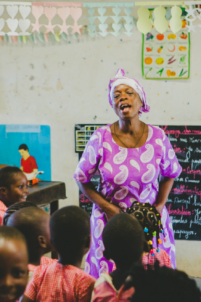 écoliers béninois en uniformes à lokossa chantent et dansent avec une institutrice,mission humanitaire