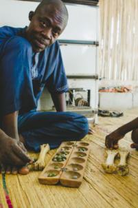 roger akodjenou gérant de l'orphelinat et du restaurant chez les amis joue à l'awalé,mission humanitaire