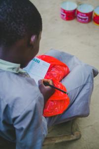 enfant béninois écrit les scores d'un jeu,mission humanitaire