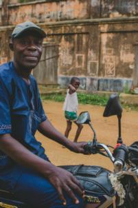 roger akodjenou gérant de l'orphelinat et du restaurant chez les amis sur une moto,mission humanitaire