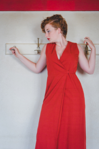 femme en robe longue accrochée à des patères d'école,rousse et rouge